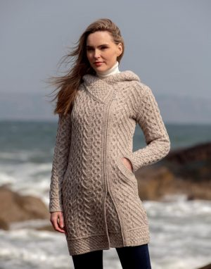 Beautiful heart design pattern coat with hood. Side zip closure and insert pockets for added comfort. Knitted with a mixture of traditional aran cable stitches with a heart design pattern giving this beautiful coat a unique design feature. Also features a Celtic trinity knot design on the zipper. Wonderful piece of Irish Knitwear.